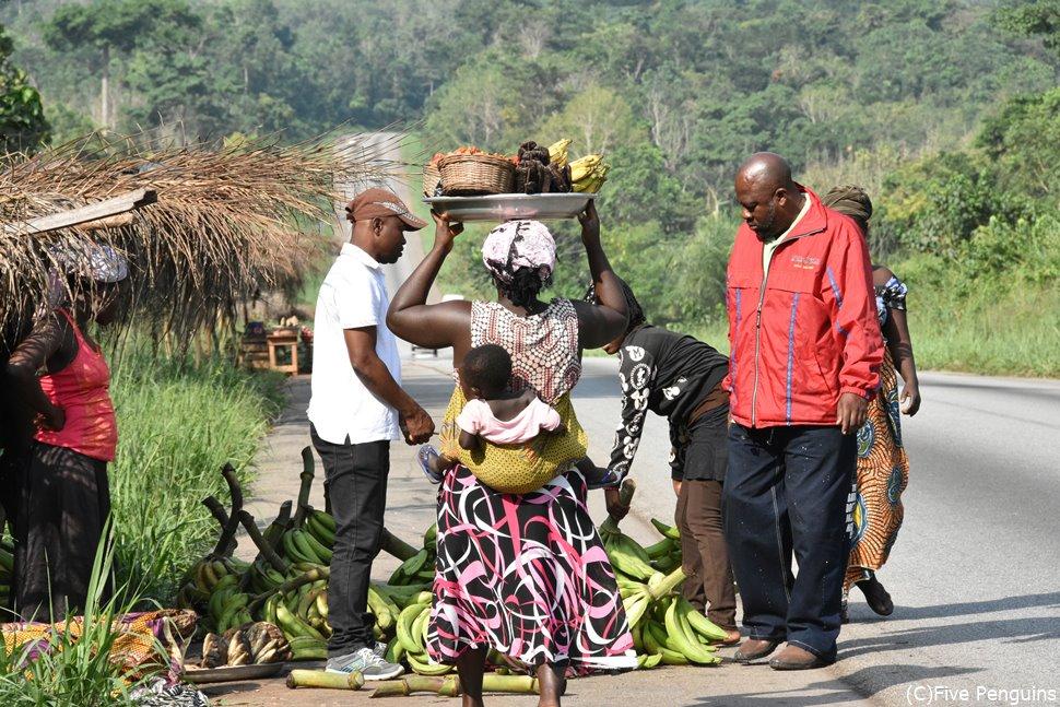 クマシの郊外でガイドが大量のバナナを買っていた