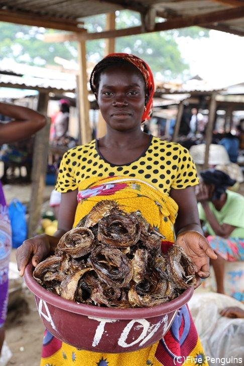 アビジャンのフィッシュマーケットで干し魚を売る女性